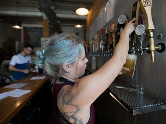 Tara Odom pours a beer from one of the 37 taps Choice City Butcher & Deli offers, including a homemade rootbeer, for a customer Thursday, September 1, 2016.