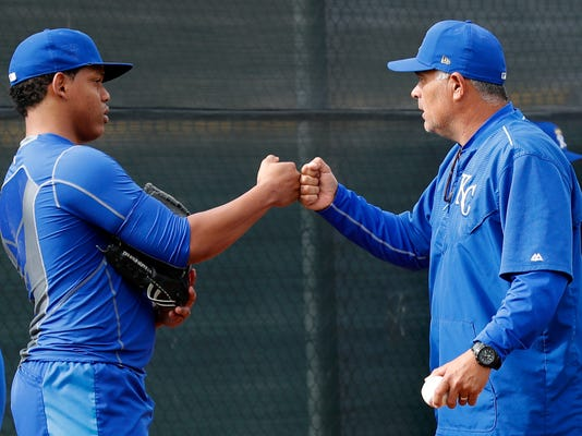Pitcher Gustavo Tejeda, left, fist bumps with rehab pitching coach Carlos Reyes, right, during a Kansas City Royals baseball spring training workout, Tuesday, Feb. 13, 2018, in Surprise, Ariz. (AP Photo/Charlie Neibergall)