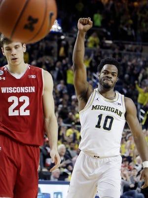 Michigan guard Derrick Walton Jr. raises his fist next to Wisconsin forward Ethan Happ after a basket during the second half Thursday night.