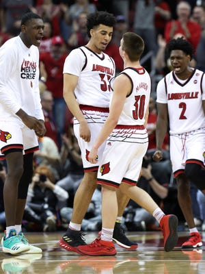 U of L's Jordan Nwora (33), center, celebrates with Ryan McMahon (30) after McMahon hitting a flurry of 3-point shots against MTSU during the NIT at the Yum Center in Louisville.    Mar. 18, 2018