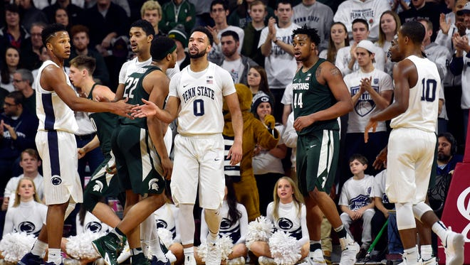 Penn State forward Payton Banks (0) high-fives forward Lamar Stevens after a score against the Michigan State during the first half Saturday at the Palestra, as MSU's Miles Bridges, left, and Nick Ward, right, communicate in hindsight.