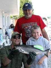 FILE – Photo from the 2019 Kids' Fish Derby. Pictured: Volunteer Brian Robinson (left) holds the fish caught by Little Brother Mark (right) and his Big Brother Leon LeClair (standing, rear).