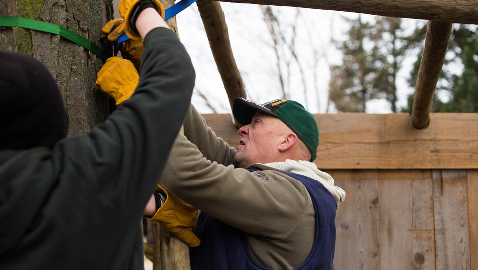 Doug Stanton tightens the straps securing the manger