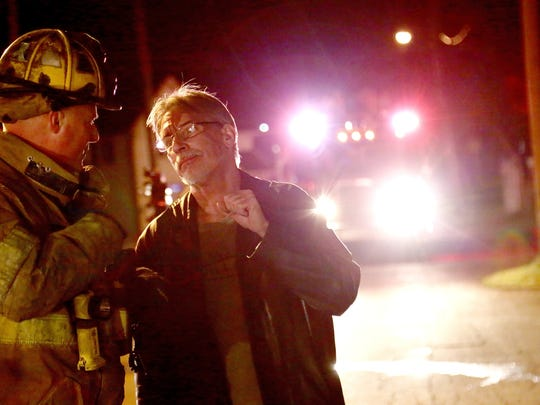 Gary Best talks to a firefighter after a fire at 402 St Clair St, Mansfield Monday night. Best lives there with 4 other people.