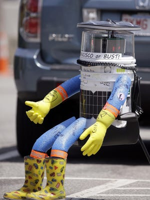 HitchBOT, a hitchhiking robot, waits for a passing motorist to pick it up Friday, July 17, 2015, in Marblehead, Mass. HitchBOT is began cross-country hitchhiking trip of the U.S. in Marblehead with a final destination goal of reaching San Francisco.