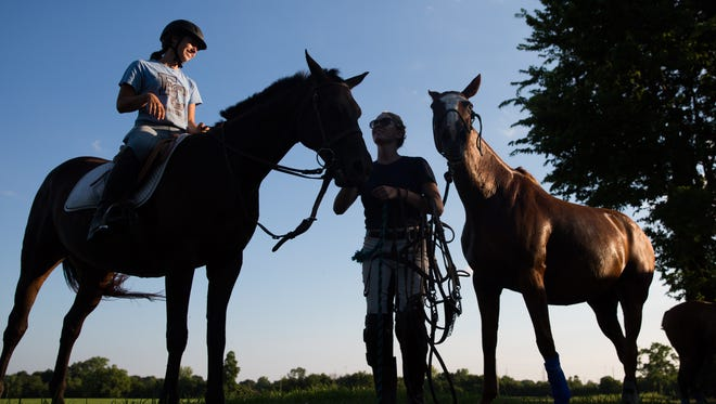 Lucia Burton, left, a groom, exercises June while Julia Naber prepares to wash down Leona after polo practice at Oxmoor Farm. July 25, 2017.