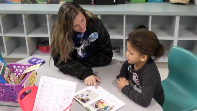 First grader Krystyna Pouncey (right) and Merritt Island High ninth grader Savannah Jordan work together during a new reading program at Lewis Carroll Elementary.
