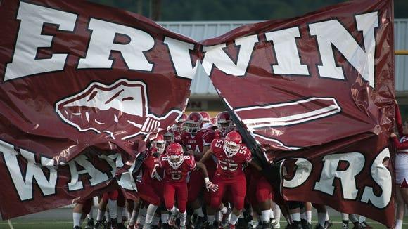 Erwin football players run through their banner Friday