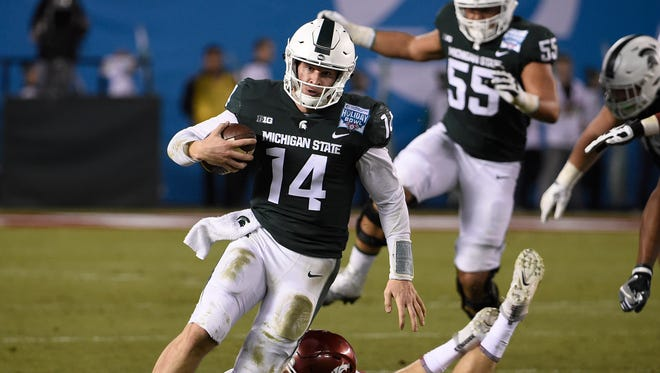 Michigan State quarterback Brian Lewerke (14) tries to break the tackle of Washington State linebacker Isaac Dotson (31) as he rushes during the first half of the Holiday Bowl NCAA college football game Thursday, Dec. 28, 2017, in San Diego.