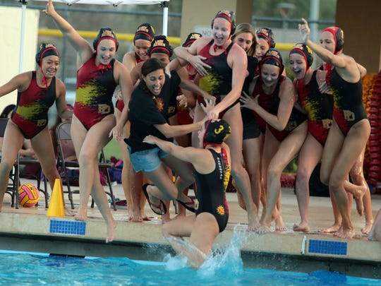 Palm Desert water polo coach Michelle Stein-Valovic takes a victory dip with her team after their DVL championship win against La Quinta on Saturday.