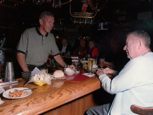 -- RUSTY FISCHER, owner of Bernard's Surf in Cocoa Beach, chats with customers, including Jim Mullen of Cocoa Beach. Fischer, president of the Brevard Restaurant Association, says paperwork associated with the state's alcohol surcharge is too time-consuming.