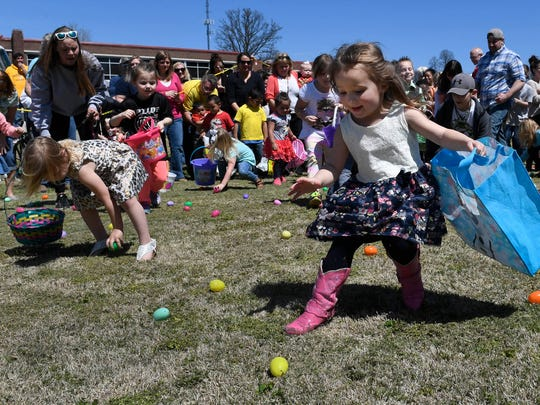 The stampede is on as children scramble for some of the 12,000 eggs at the West Side Nut Club's 70th Annual Easter egg hunt at Evansville's Mater Dei High School Saturday, April, 8, 2017.