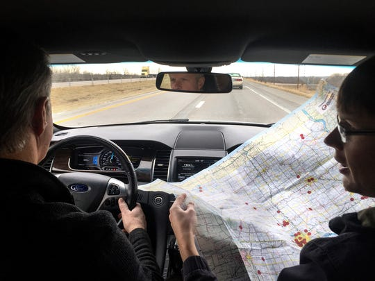 Clint Bailey, left, drives north on I-35 as his son Marc goes over a state map of the breweries they have traveled to this year Thursday, Dec. 15, 2016.