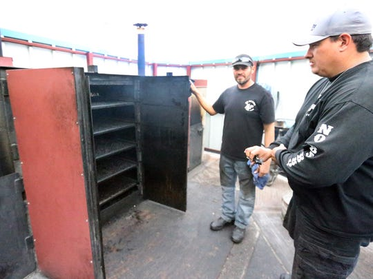 """Brehan """"Bob"""" Goodwin, right, one of the owners of No BS BBQ, and pit master Joe Martinez work with  the eatery's outdoor smoker."""
