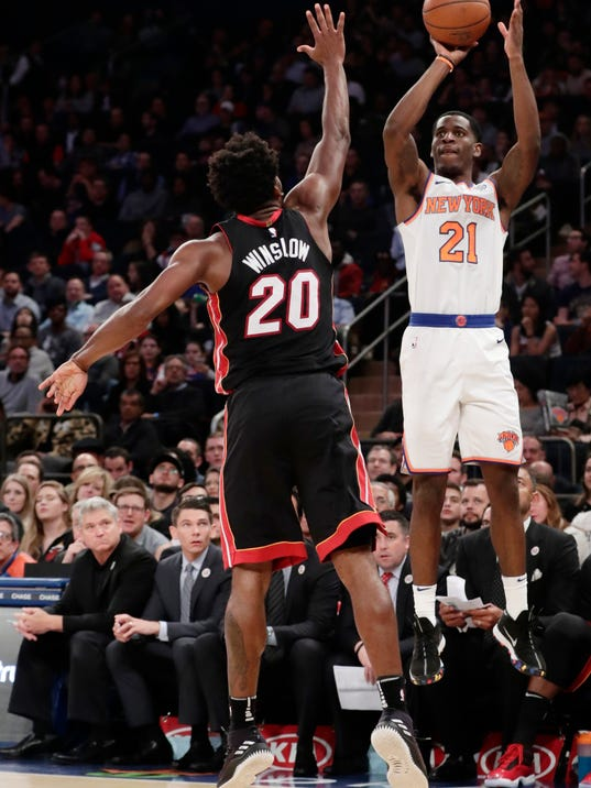 New York Knicks' Damyean Dotson (21) shoots a 3-point basket over Miami Heat's Justise Winslow (20) during the second half of an NBA basketball game Friday, April 6, 2018, in New York. The Knicks won 122-98. (AP Photo/Frank Franklin II)
