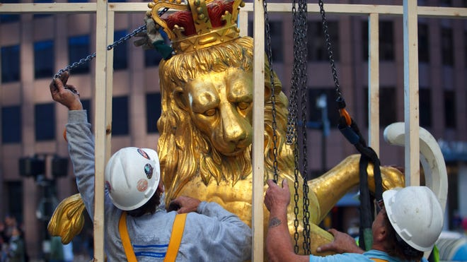 A lion statue is removed from atop the Old State House on Washington Street in Boston. A  time capsule from 1901 was tucked inside the statue.