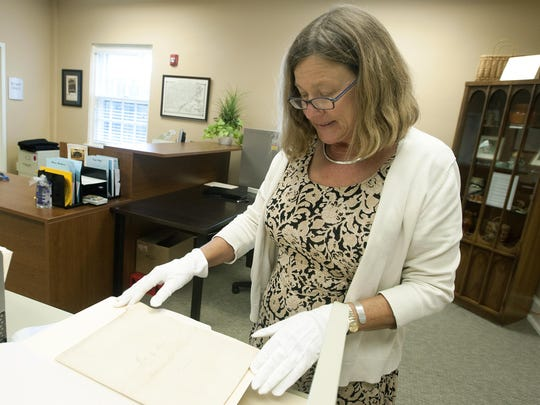 Sarah Downing, with the Western Regional Archives at the State of North Carolina Department of Cultural Resources, looks through items that came out of the 1897 Vance Monument time capsule.