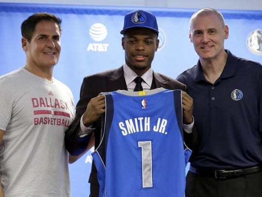 Dallas Mavericks team owner Mark Cuban, left, and head coach Rick Carlisle, right, present their choice at No. 9 from Thursday's NBA Draft. Dennis Smith Jr., center, with his team jersey during a news conference, Friday,  in Dallas.