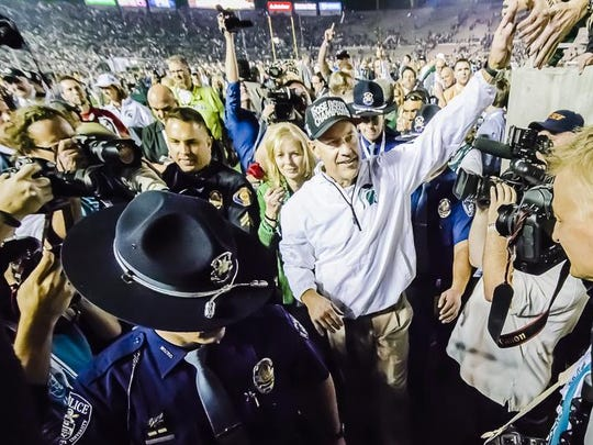 MSU Football Head Coach Mark Dantonio greets fans as he leaves the field after the Spartans' win over Stanford at the 2014 Rose Bowl Jan. 1, 2014 in Pasadena, Calif.