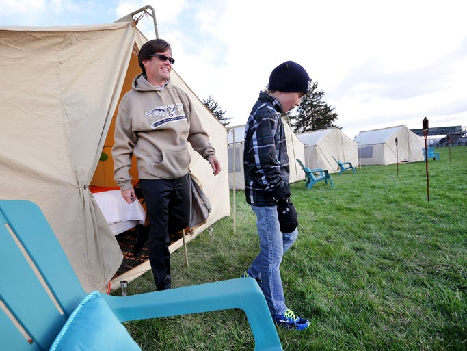 "Indianapolis Motor Speedway President Doug Boles and his son Carter Boles, 11, get set to check out the ""Glamping"" site after getting set up in their tent that houses a queen bed and night stands before spending the night at the speedway on Tuesday, April 15, 2014. The glamorous tents, ranging from $650-$1100, will be available to campers three days before the race. The price includes tickets to the race as well as Carb Day and Legends Day."