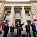 Lee County Commissioner Frank Mann, center, celebrates the 100 year anniversary of the Old Lee County Courthouse with the public and other commissioners who include, Brian Hamman, Larry Kiker, John Manning and Cecil Pendergrass.  On the far left is Clerk of Court, Linda Doggett.  A time capsule will be filled with memorabilia and placed into chamber in the courthouse.