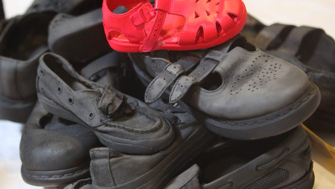 A child's  red shoes stand out in a pile of black shoes in  Holocaust artwork that was displayed  during a 2011 Holocaust Essay and Art Contest at Temple Israel.