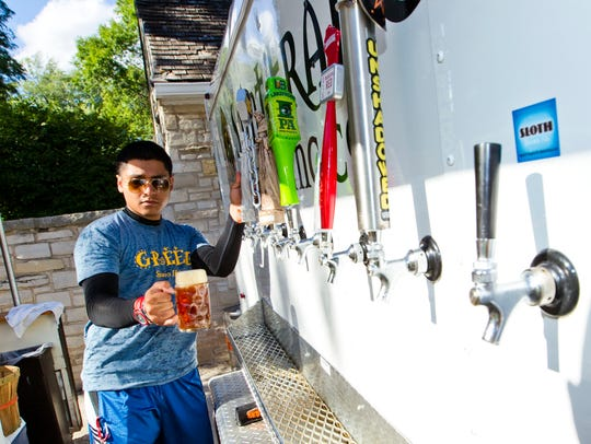 Allan Rodriguez pours a beer at Humboldt Park Beer