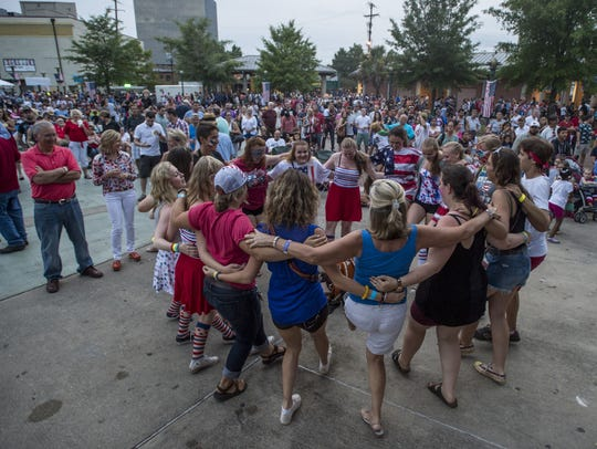 A group of Norwegian tourists dance in a circle during