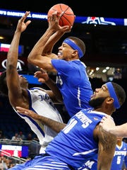 Memphis forward Jimario Rivers (middle) grabs a rebound away from Tulsa defender Junior Etou (left) as Mike Parks Jr., (right0 falls to the ground during first half action of their AAC second round tournament game in Orlando, Fl., Friday, March 9, 2018.