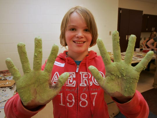 Hannah Cole of Ankeny shows off green grout on her hands after working on a mosaic mural in 2011 at Ashland Ridge Elementary School in Ankeny. The Metro Arts Alliance activity was led by local artist Concetta Morales.