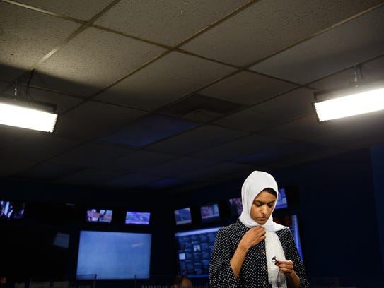 Tahera Rahman reaches under her headscarf to place