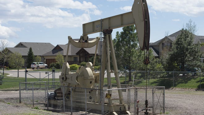 A pump jack rig, used in oil extraction methods, is surrounded by homes in the Hearthfire neighborhood in north Fort Collins.
