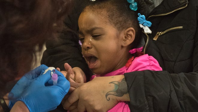 "Flint's Breeze Harden, 3, breaks into tears as she is tested for lead with her mother Darlene Harden, ""I'm very nervous, I don't want my child to have lead. I don't want none of the kids to have lead."""