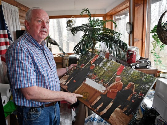 Retired Col. Gerald York shows a photo taken as he