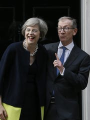 New British Prime Minister Theresa May and her husband Philip May smile from the steps of 10 Downing Street in London, Wednesday July 13, 2016.