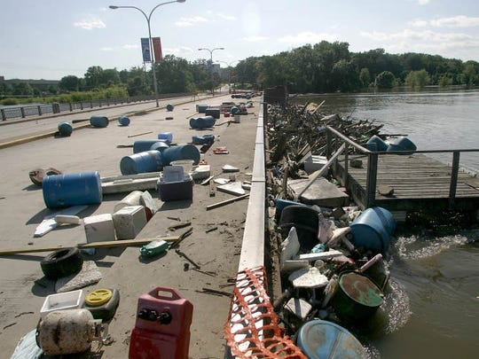 Debris is washed up against and scattered across the Park Road bridge in Iowa City as the water level of the Iowa River slowly recedes from record-setting flood levels on Tuesday evening, June 17, 2008.