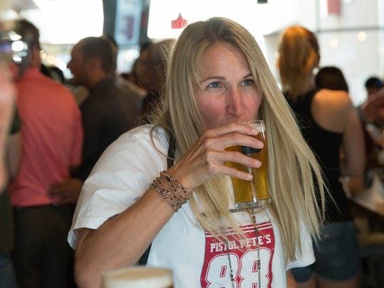 """Heidi Moccia, wife of New Mexico State University's Athletic Director Mario Moccia, takes a sip of the new """"Pistol Pete's 1888 Ale"""" brewed by Bosque Brewing Co. in conjunction with NMSU. The beer is on tap at Bosque Brewing Company's taproom and will be available in cans in  2018. Thursday Aug. 17, 2017."""