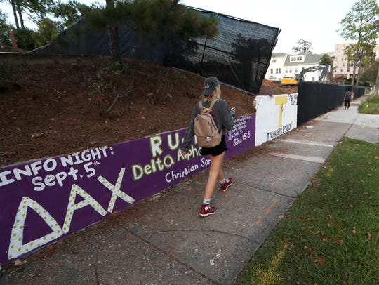 A student walks by a sorority's mural on FSU campus,