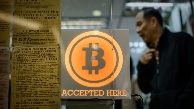 A man walks out of a shop displaying a bitcoin sign during the opening ceremony of the first Bitcoin retail shop in Hong Kong.