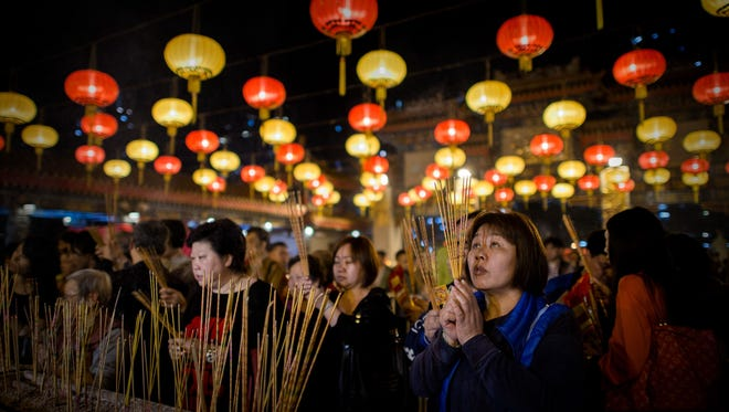 Worshipers burn incense and pray at the Wong Tai Sin Temple to welcome the Year of the Horse in Hong Kong. Tens of thousands of worshipers flocked to temples across to pray for good luck and fortune for the new year.