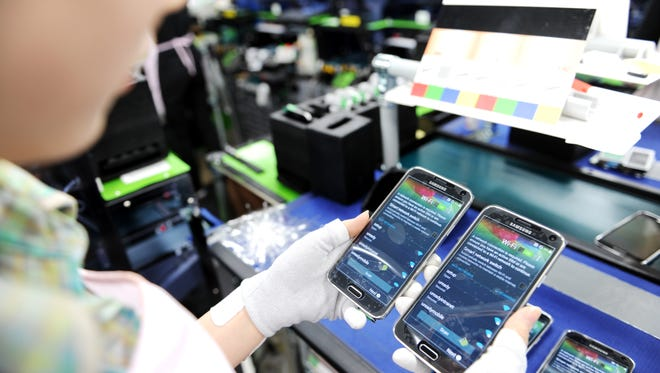 A Samsung factory worker examines Galaxy S5 smartphones.