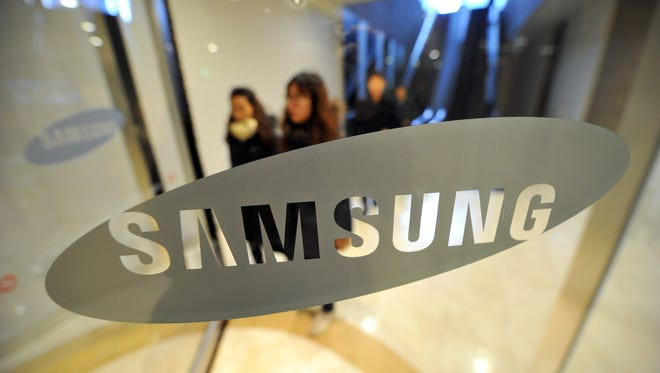 In a file picture taken on January 24, 2014 pedestrians walk past a logo of Samsung Electronics at the company's headquarters in Seoul.