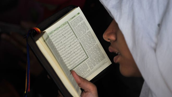 An Indonesian Muslim woman reads a copy of the Quran at the Istiqlal grand mosque in Jakarta on May 4, 2014.
