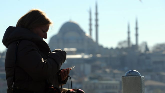 A Turkish woman looks at her smart phone in the Eminonu district of Istanbul.