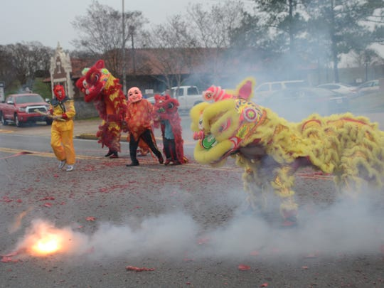 Members of the local Vietnamese community celebrate the Vietnamese New Year, or Tet, at City Hall in downtown Alexandria on Sunday. Members dressed as a monkey, Buddha and dragons and danced among fireworks. This holiday is considered the most important among Vietnamese.