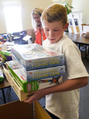 Franklin 13-year-old Gytis Snyder packs toys into a boxes that will be shipped to the Lithuanian orphanage where he grew up.