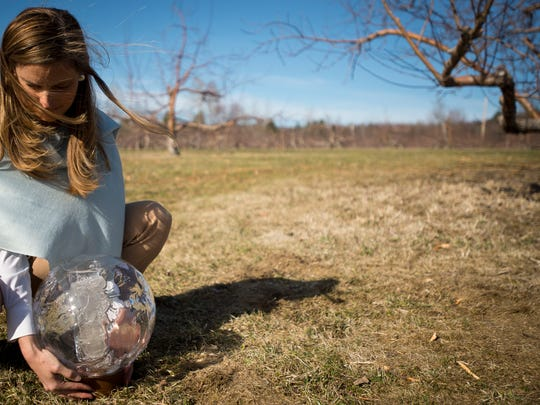 Shyla Nelson takes a moment to rest after holding a new glass globe that houses shards of a shattered glob inside in a glass cylinder and rests of a turned wood base. The entire piece weighs about 12 pounds and will be carried by Nelson on a trip to Paris to urge world leaders to do more to protect the environment.