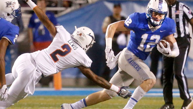 MTSUÕs Reed Blankenship (12) runs the ball as UTEPÕs Terry Juniel (2) dives for a tackle during the game against UTEP, on Saturday, Nov. 4, 2017, at MTSU.