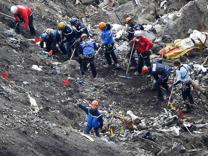Rescue workers look over debris from the Germanwings