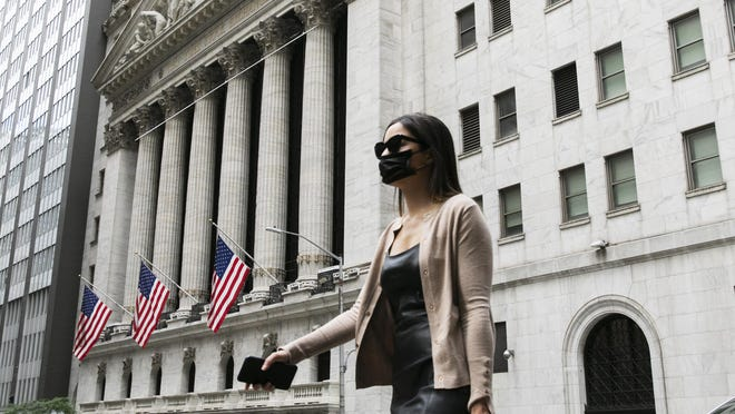 A woman wearing a mask passes the New York Stock Exchange, Tuesday, June 30, 2020, during the coronavirus pandemic.